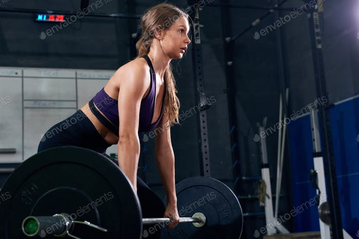 Straining Woman Lifting Heavy Barbell