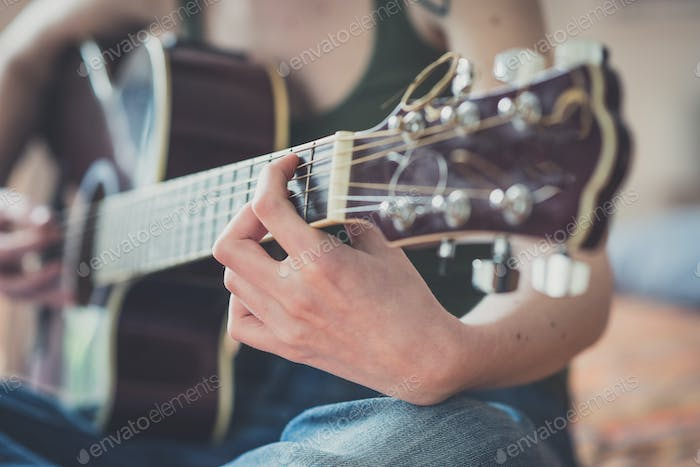 close up of woman hands playing guitar