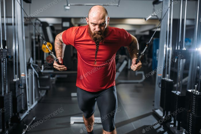 Strong athlete, training on exercise machine