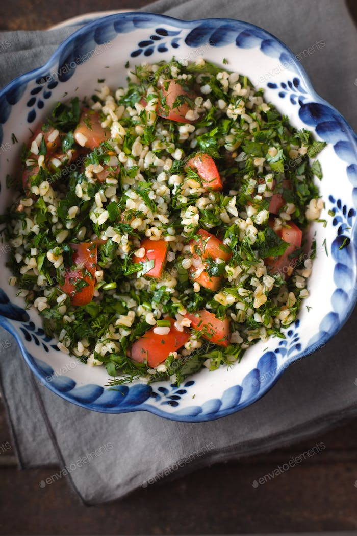 Tabouli salad in the ceramic bowl top view