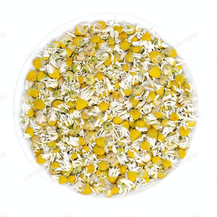 Dried chamomile blossoms, camomile tea in white bowl