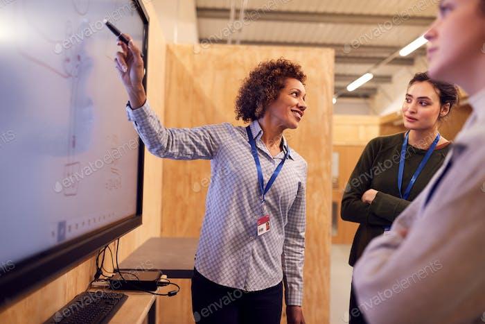 Tutor mit Auszubildenden Elektriker Studieren Für Lehrlingsausbildung Blick auf Schaltplan auf Bildschirm