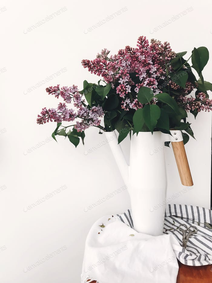 Beautiful lilac flowers in white stylish watering can