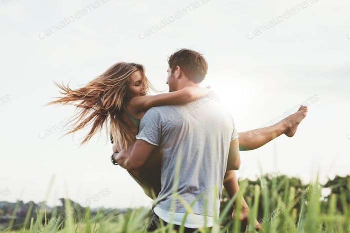 Mann tragen Freundin im Gras Feld