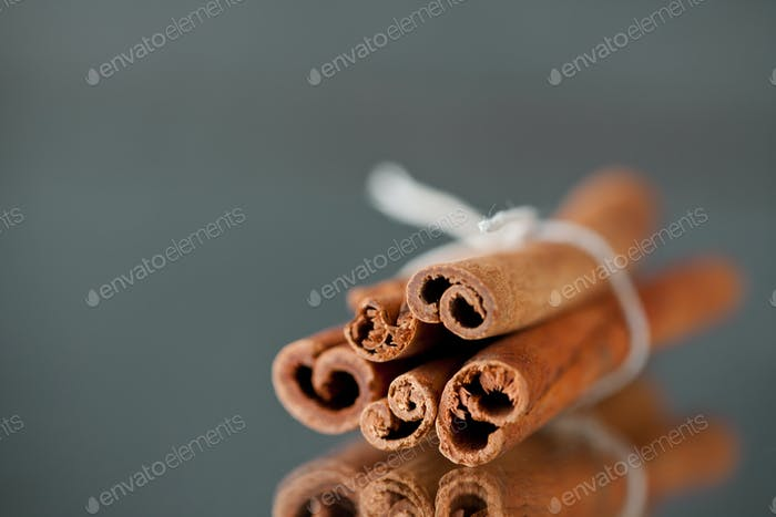 Bundle of cinnamon against a grey background