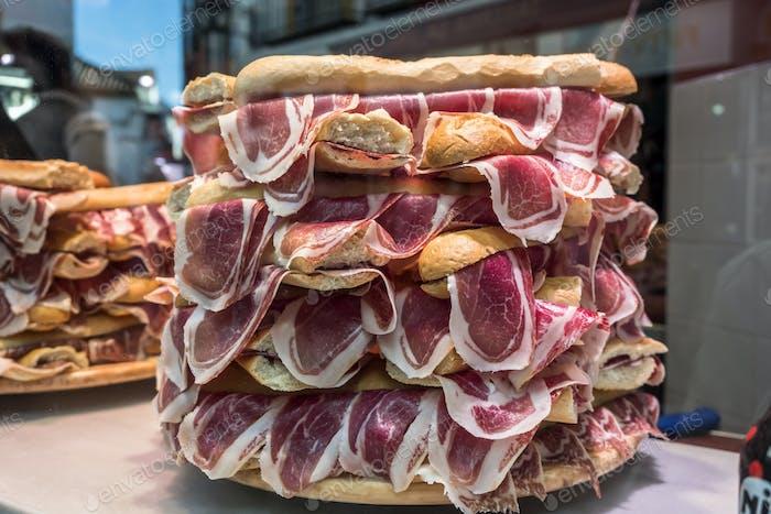 Mehrere Jamon Serrano Sandwiches stapelten sich in einem Schaufenster, konzeptionelles Bild