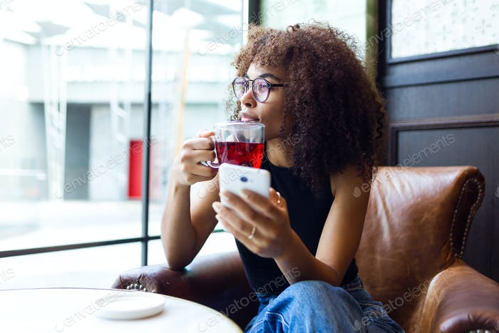 Beautiful young woman drinking coffee in cafe.