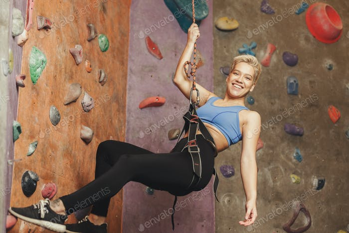 Young woman climbing artificial rock wall at gym