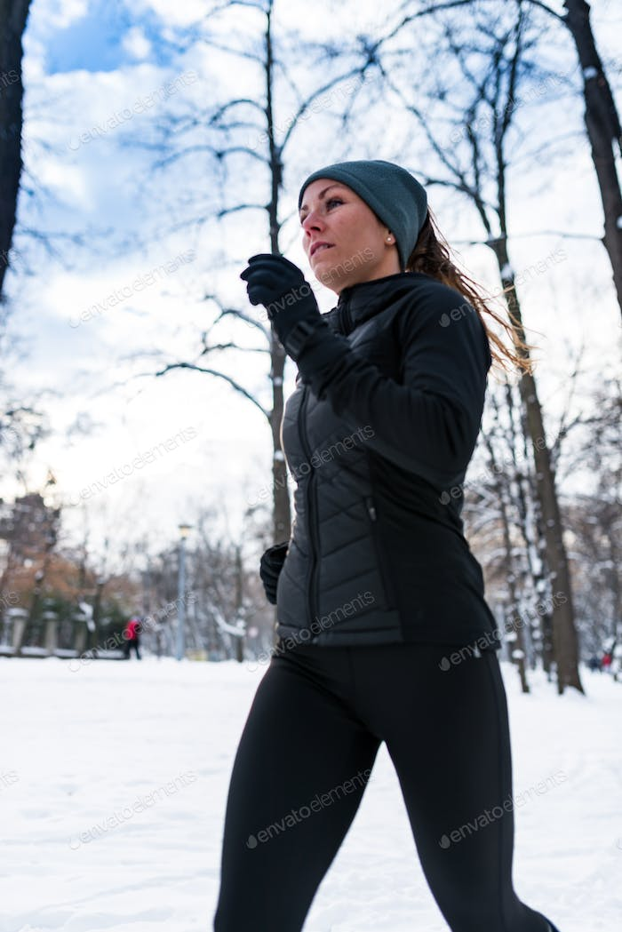 Sportlerin Joggen im Park im Winter