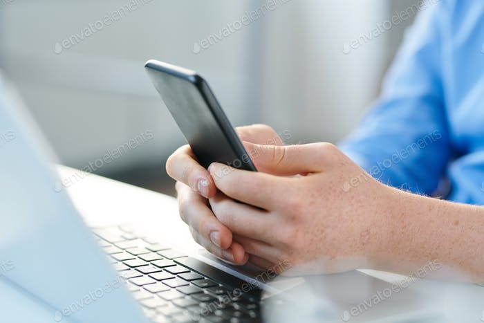 Hands of young man with mobile gadget over laptop keypad
