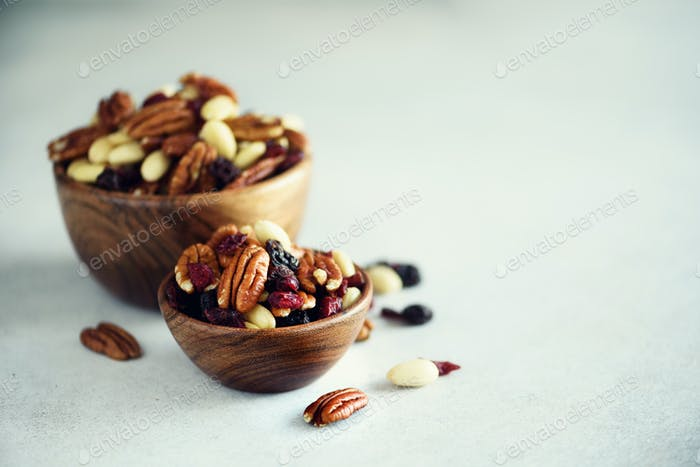 Mixed nuts and raisins in wooden bowl. Healthy food and snack. Walnut, pistachios, almonds