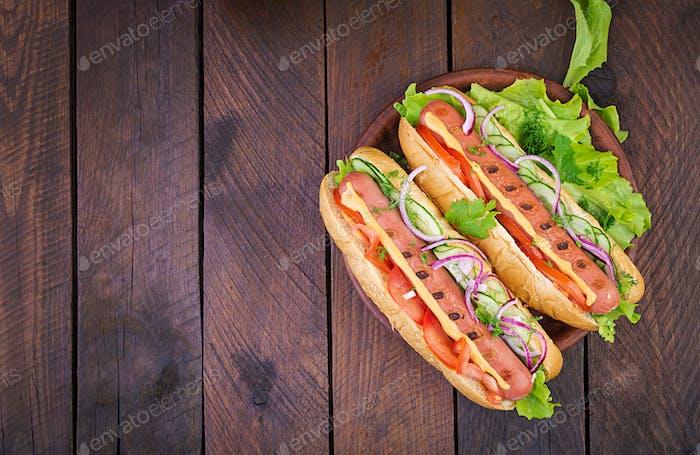Hot Dog mit Wurst, Gurke, Tomaten und Salat auf dunklem Holzhintergrund.
