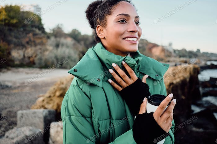 Pretty cheerful African American girl in down jacket with cup to go happily looking away on seaside