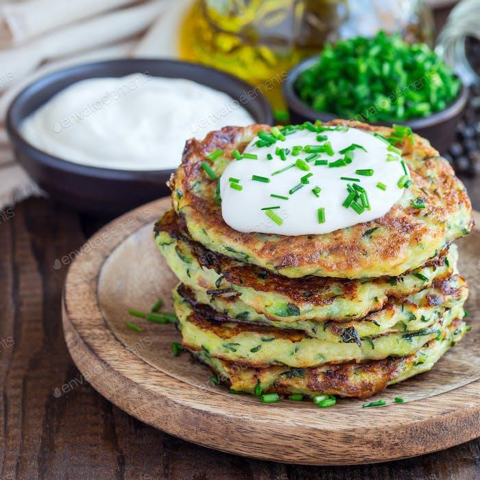 Vegetarian zucchini fritters or pancakes, served with greek yogu