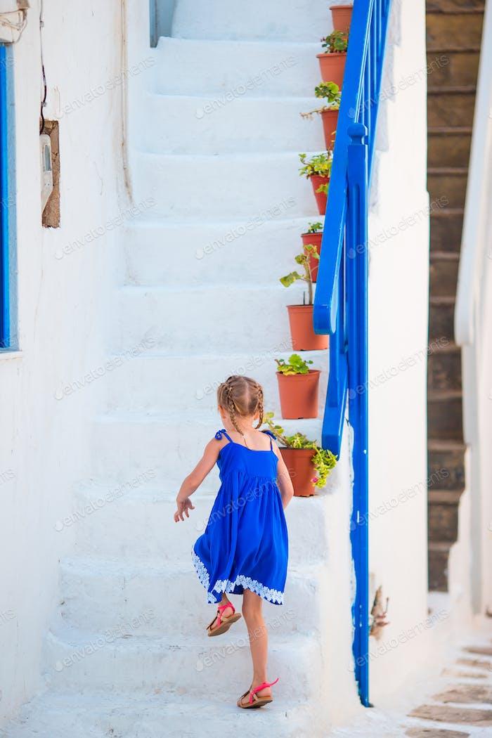 Niedliches Mädchen in blauem Kleid auf der Straße des griechischen Dorfes auf Mykonos Insel, in Griechenland