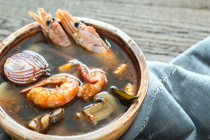 Schüssel mit Thai Tom Yum Suppe auf dem Holztisch