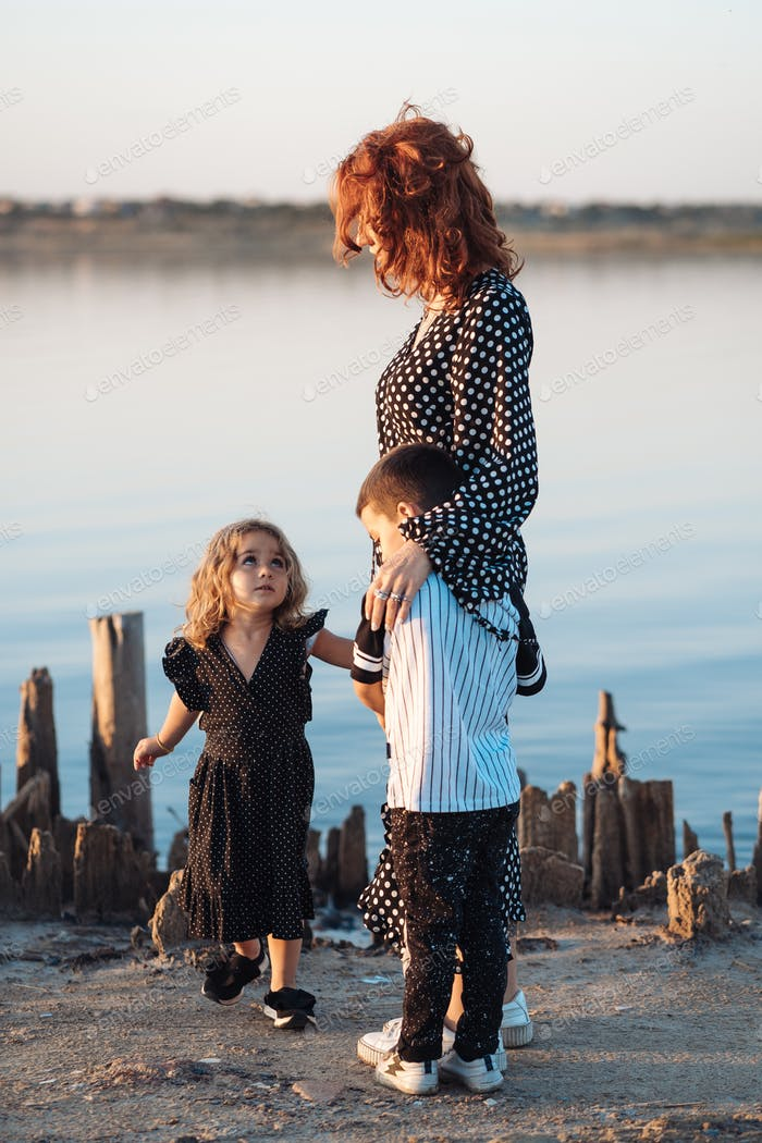mother walks with children on the beach