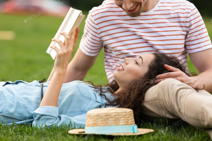Image of smiling couple man and woman 20s lying on green grass i