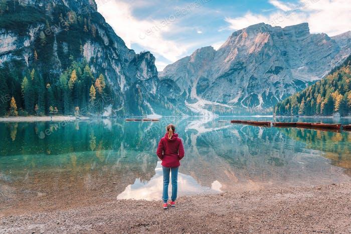 Frau in roter Jacke steht an der Küste des Prags Sees