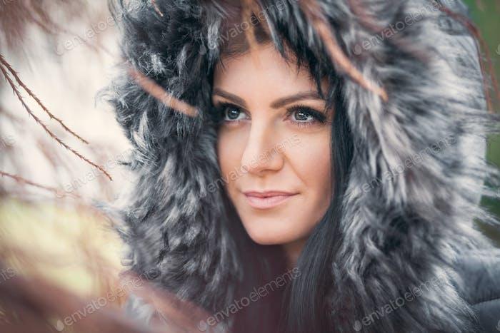 Beautiful woman wearing a fur hood winter coat