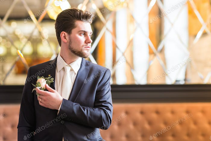 Groom in a suit holding buttonhole