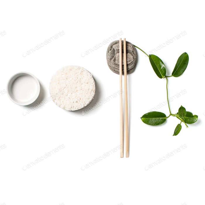Composition with white rice and chopsticks on white background.
