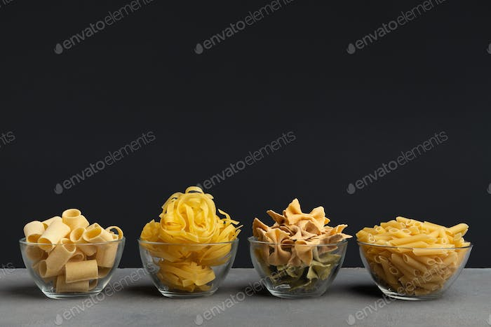 Various kind of pasta in glass plates on black background