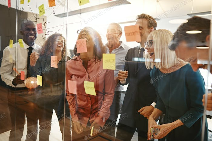 Diverse group of businesspeople laughing during an office brainstorming session