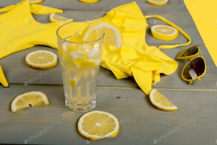 Gelber Badeanzug einteilig, Piloten-Sonnenbrille und Limonade zwischen Teilen Zitronen auf grauem Holz