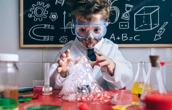 Счастливый ребенок делает эксперименты с мыльной пеной