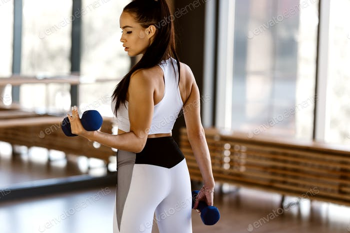 Athletic dark-haired girl dressed in white sports top and tights holds dumbbells