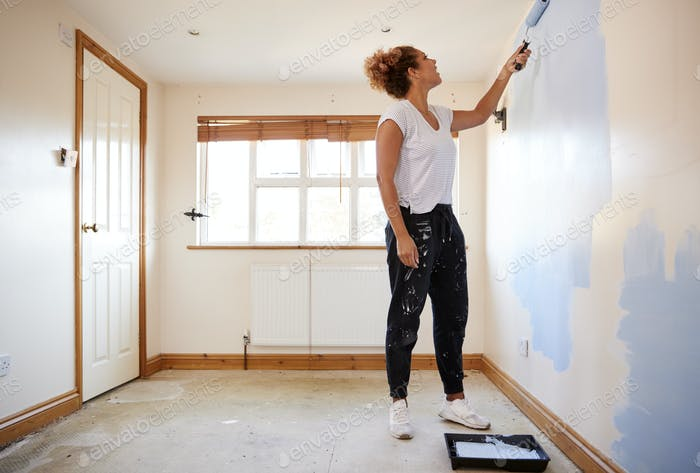 Woman Decorating Room In New Home Painting Wall