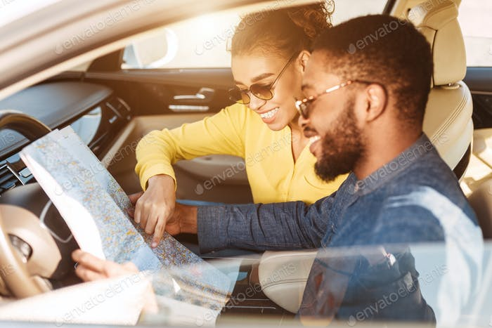 Travel Concept. Afro Couple Using Map In Car