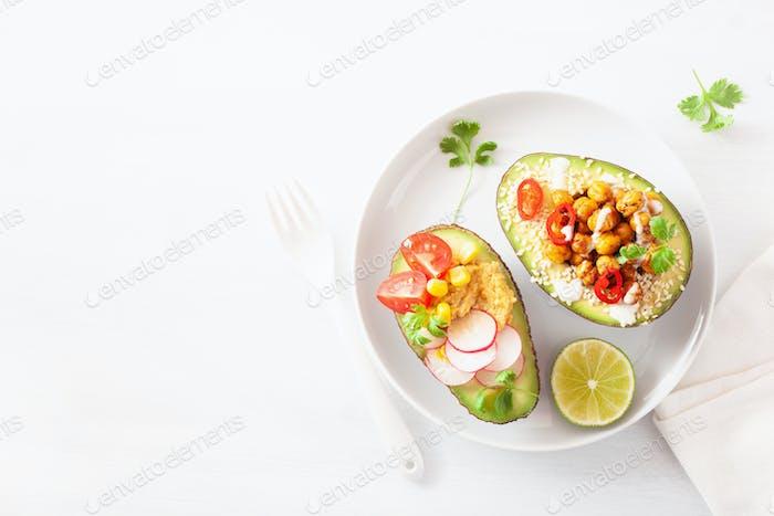 avocado boats stuffed with hummus, tomatoes, radish, roasted chi