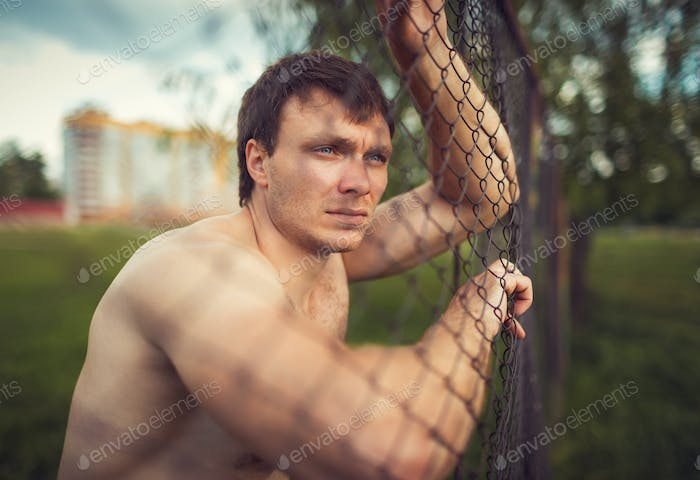 Young athletic guy near the netting