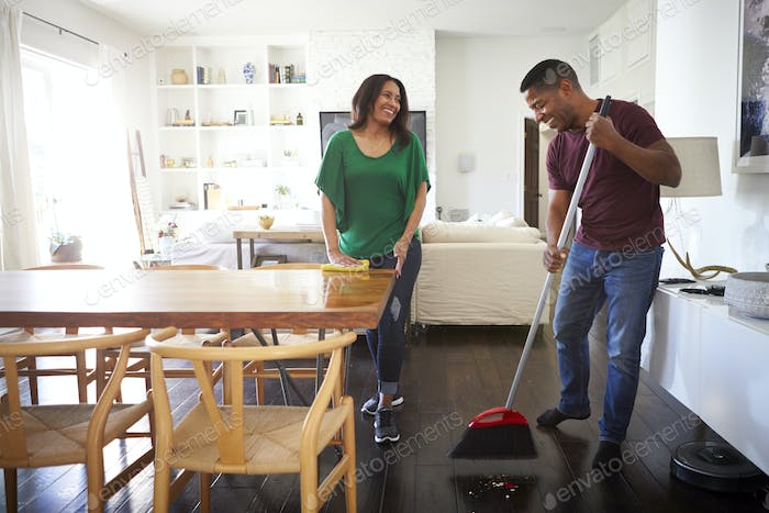 Millennial man sweeping the floor in the dining room while his partner stands talking to him