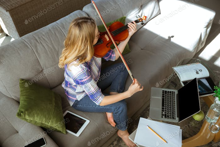 Young woman studying at home during online courses or free information by herself, playing violin