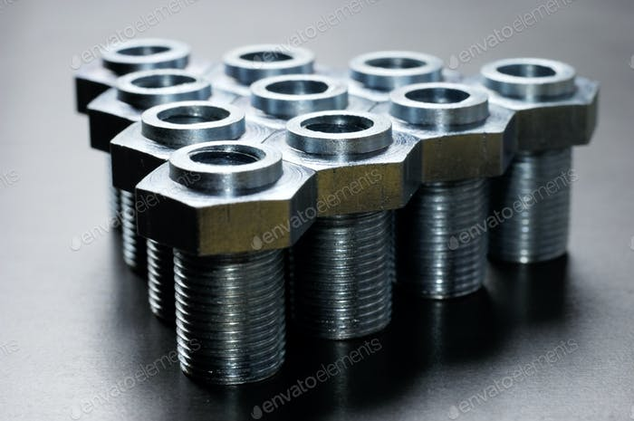 Close-up of several chrome metal bolts