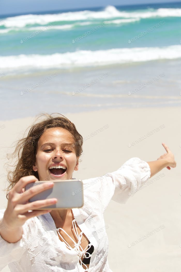 Young woman taking selfie and pointing to the sea