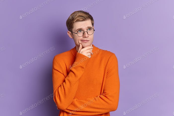 Portrait of blue eyed guy ponders on something stands in thoughtful pose holds chin concentrated int