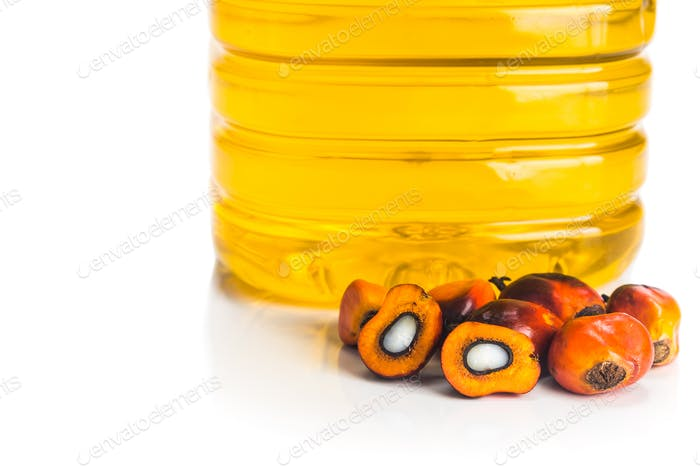Refined palm oil in bottle with fresh oil palm fruits.
