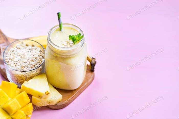 Mango, Banane, Ananas und Haferflocken Smoothie im Glas