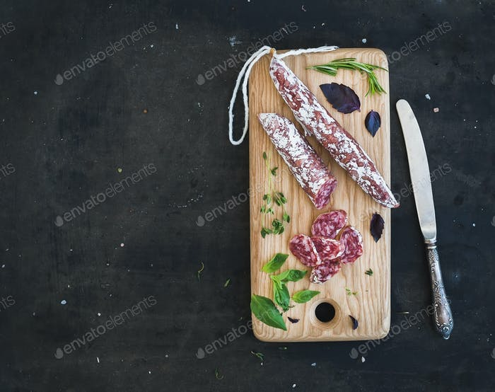 Meat gourmet snack. Salami, garlic and herbs on rustic wooden board over dark grunge backdrop