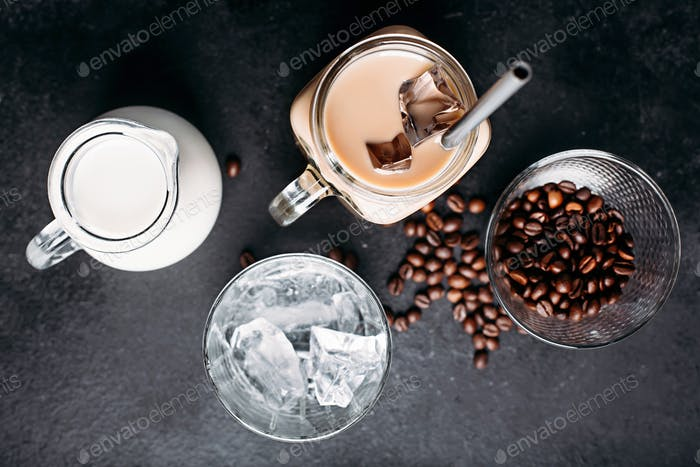 Cold iced coffee with ingredients: ice cubes, milk, coffee beans