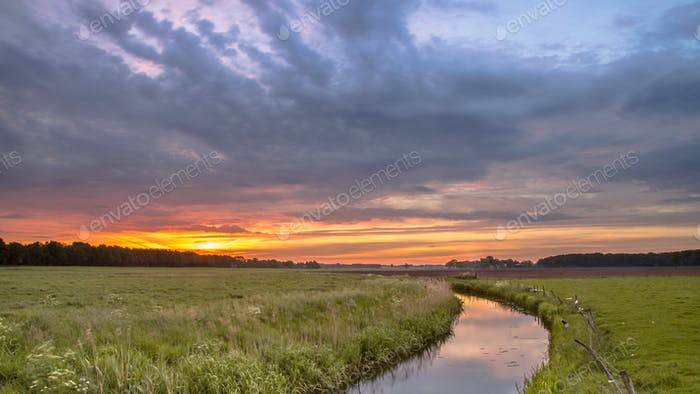 Sunrise over lowland river valley landscape