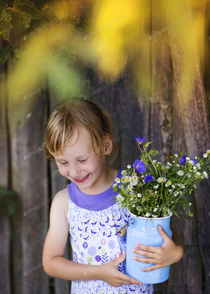 Cute little girl with flowers laughing