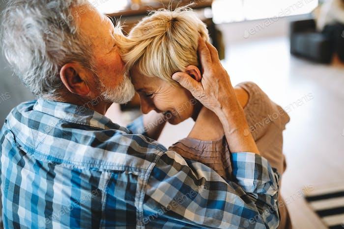 Glückliche lächelnde ältere Paar umarmen zusammen zu Hause