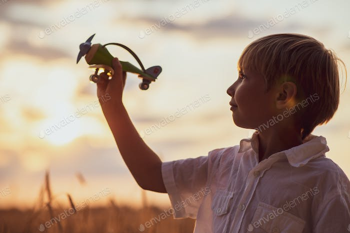 Boy in a  white shirt with a plane in hands against sky.