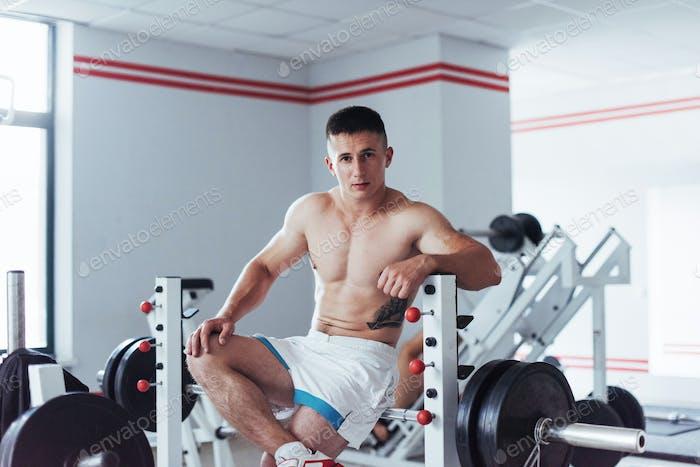 Retrato de un hombre guapo haciendo ejercicios en el gimnasio