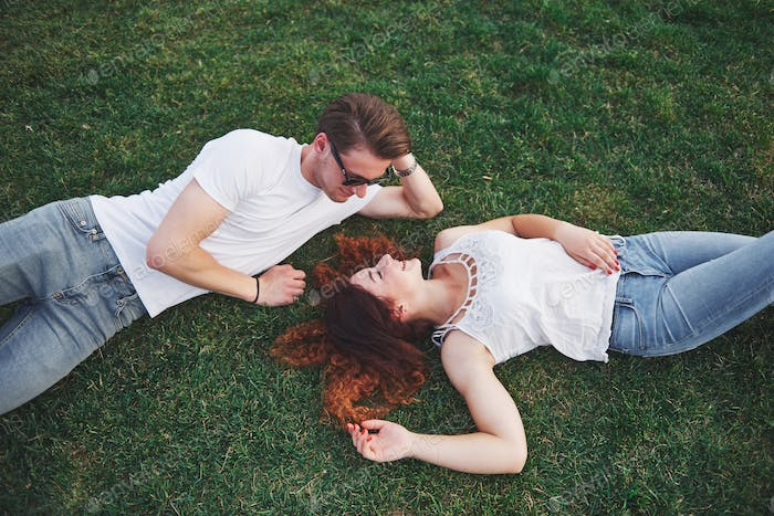 A romantic couple of young people lying on the grass in the park. Top view
